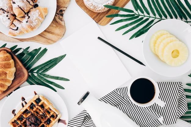 Lápiz y papel en blanco en el centro del desayuno en el escritorio blanco Foto gratis