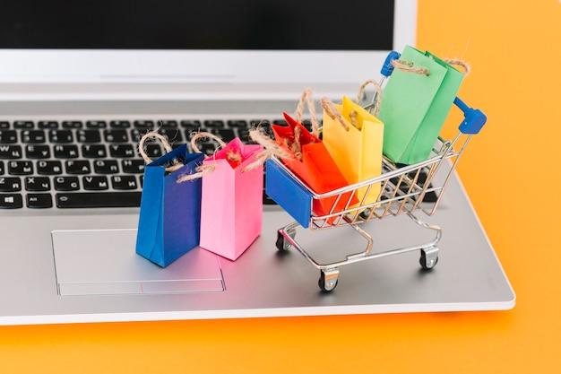 Laptop con carrito de compras y paquetes de juguetes. Foto gratis
