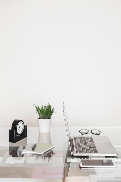 Laptop cerca de smartphone y reloj en mesa Foto gratis