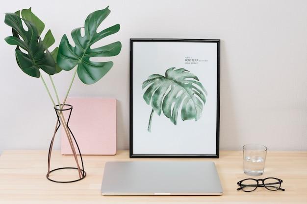 Laptop con foto y vasos en mesa Foto gratis