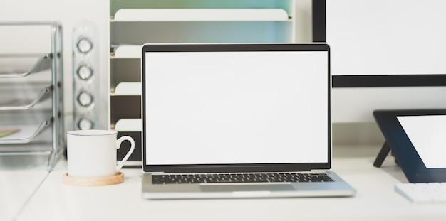 Laptop con pantalla en blanco en un lugar de trabajo cómodo con suministros de oficina y taza de café Foto Premium