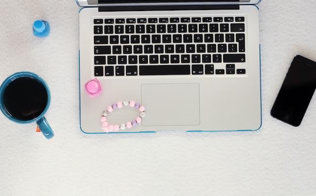 Laptop, teléfono inteligente, taza y esmalte de uñas Foto gratis