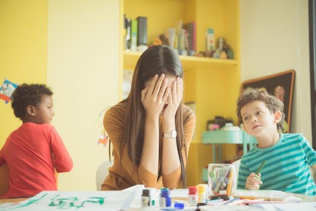 Las manos asiáticas del jardín de infantes del profesor cerraron ambos oídos de ella en un trastorno de fracasado quell quited travieso, de los muchachos en clase en el argumento de los cabritos del preescolar. Vintage efecto estilo imágenes. Foto Premium