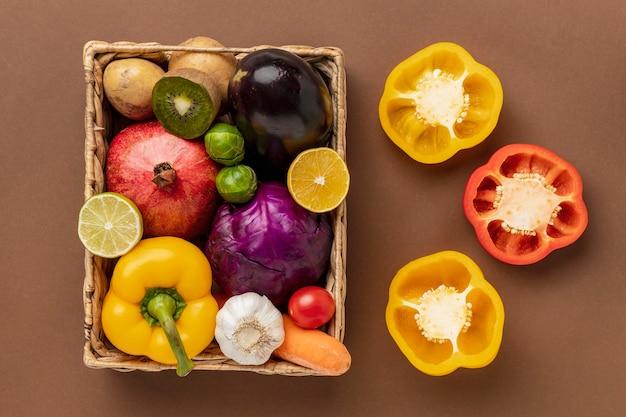 Lat plano de pimientos con cesta de verduras Foto gratis