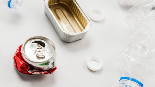 Latas y residuos plásticos sobre superficie blanca. Foto gratis