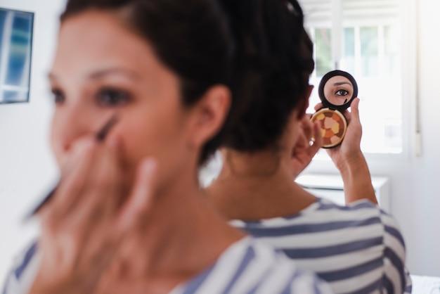 Latina joven poniéndose maquillaje Foto Premium