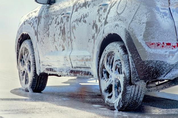 Lavado de autos. el primer automóvil está en la espuma activa. Foto Premium