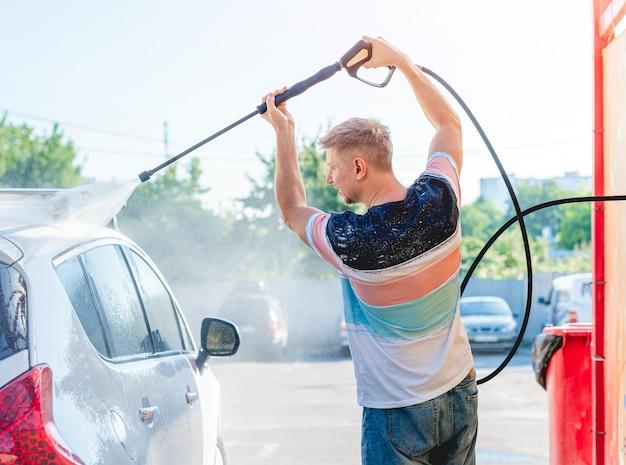 Lavar el coche con agua a alta presión Foto Premium