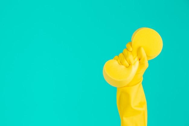 Lavavajillas con guantes amarillos sobre un azul. Foto gratis