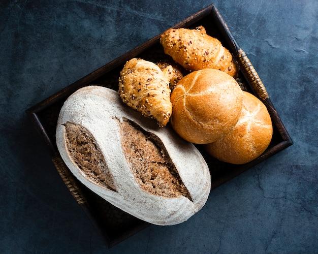 Lay flat de una cesta con pan y cruasanes Foto gratis