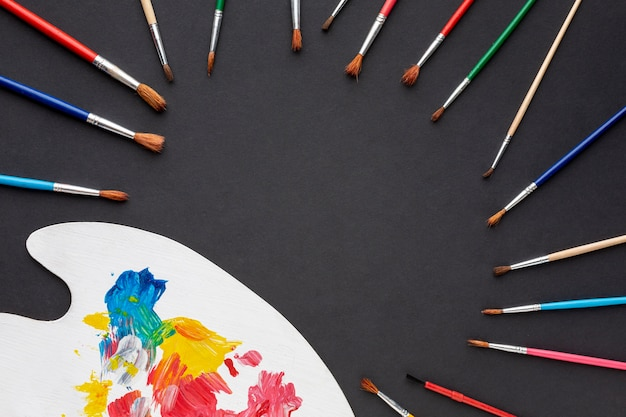 Lay flat de coloridos aquarelle y pinceles con espacio de copia Foto gratis