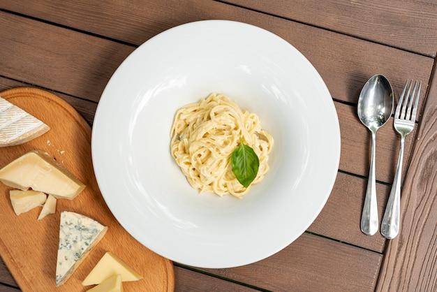 Lay flat de deliciosa pasta carbonara en mesa de madera Foto gratis
