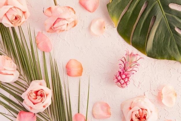 Lay flat de maqueta de espacio de trabajo tropical con hojas de monstera de palma, flores rosadas, piña y pétalos sobre pastel Foto Premium