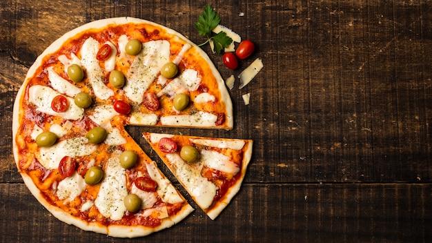 Lay flat de pizza en la mesa de madera Foto gratis