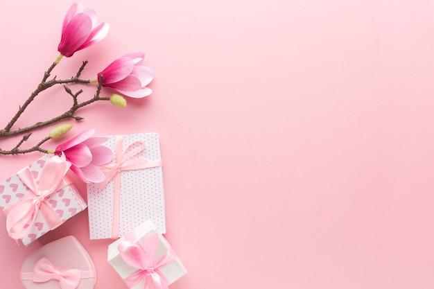 Lay flat de regalos de color rosa con magnolia y copia espacio Foto gratis