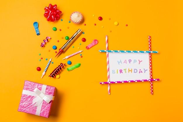 Lazo de cinta roja; aalaw; gemas serpentinas y salpicaduras de tarjeta de feliz cumpleaños y caja de regalo sobre fondo amarillo Foto gratis
