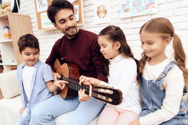 Lección de música para niños sobre cómo tocar la guitarra. Foto Premium