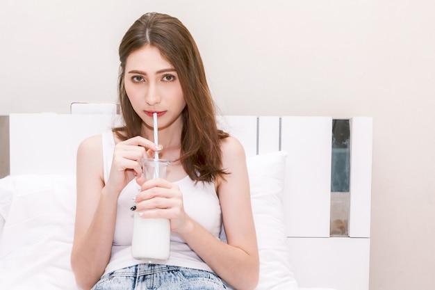 Leche de consumo de la mujer joven en su concepto bed.healthy de la forma de vida Foto Premium