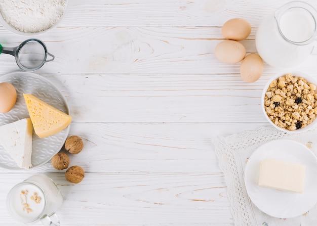 Leche; huevos; tazón de cereales queso; harina y nueces en mesa de madera blanca Foto gratis