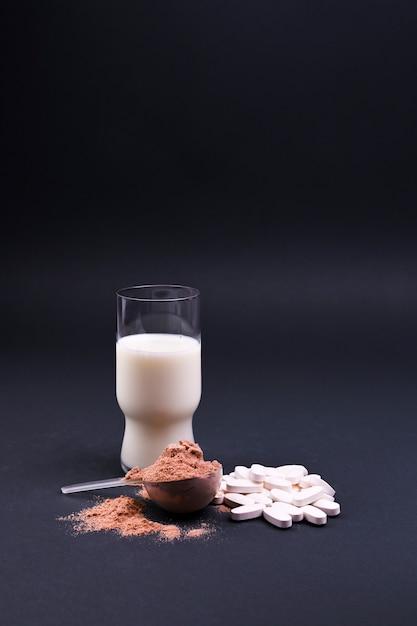 Leche y nutrición deportiva sobre un fondo negro. proteínas y complementos alimenticios. espacio libre para texto. copia espacio Foto Premium