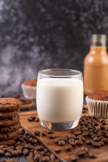 Leche en un vaso, completa con granos de café, pastelitos, plátanos y galletas en un plato de madera. Foto gratis