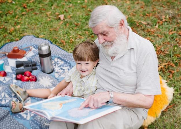 Lectura de abuelo de alto ángulo para nieto Foto gratis