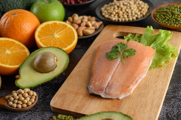 Legumbres, frutas y piezas de pescado de salmón en una tabla de cortar de madera. Foto gratis