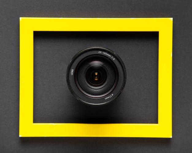 Lentes de cámara dentro de un marco amarillo sobre fondo negro Foto gratis