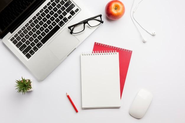 Lentes en computadora portátil, manzana, auriculares, lápices de colores, bloc de notas en espiral y mouse en el escritorio blanco Foto gratis