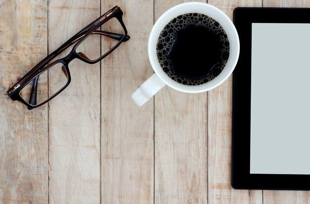 a238286154 Lentes de tableta y una taza de café en el fondo de madera   Descargar  Fotos premium