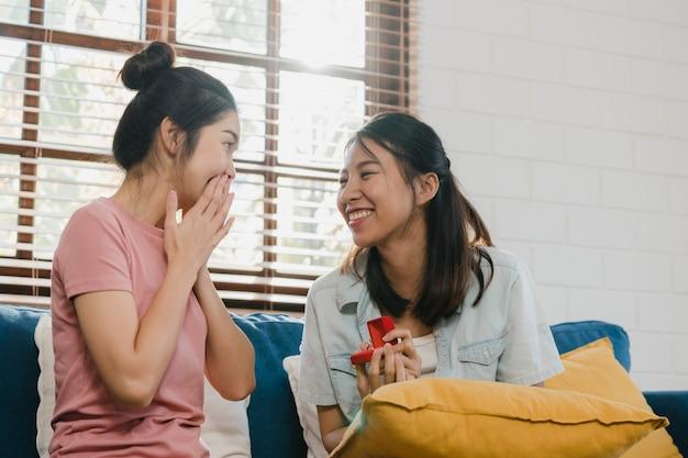 Lesbianas asiáticas lgbtq mujeres pareja proponen en casa Foto gratis