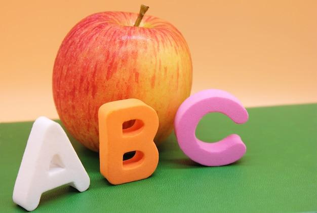 Letras del alfabeto inglés abc junto al libro y la manzana. Foto Premium