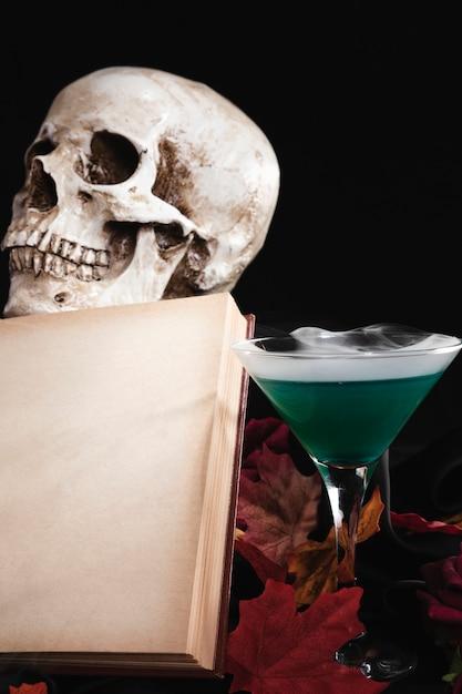 Libro abierto con calavera y bebida Foto gratis