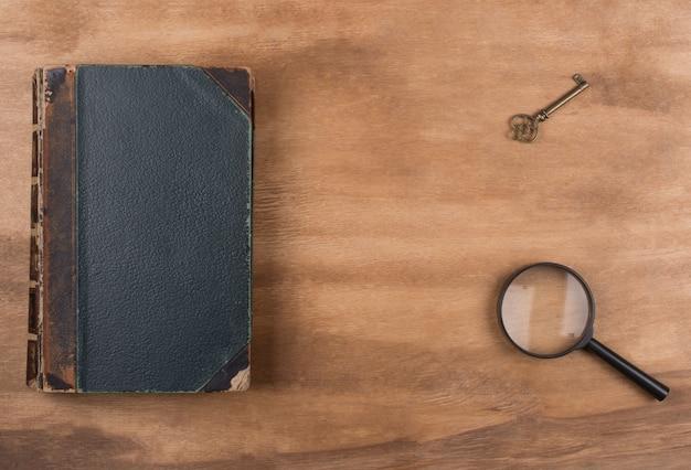 Libro antiguo, una llave y una lupa. Foto Premium