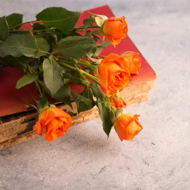 Libro antiguo y ramo de flores en superficie cutre Foto gratis