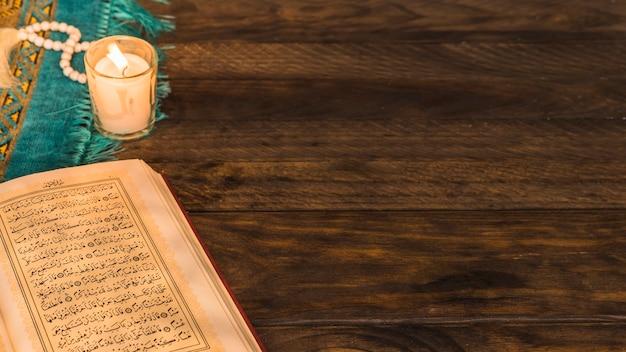 Libro árabe abierto cerca de cuentas y vela Foto gratis