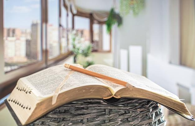 Libro biblia con primer plano a lápiz, en el de una hermosa terraza. Foto gratis