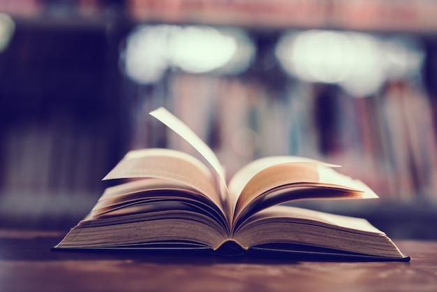 Libro en biblioteca con libro de texto abierto. Foto gratis