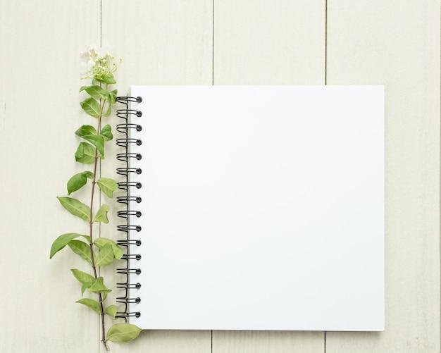 Libro Blanco En Blanco Con Una Hoja Verde. Mesa De Madera