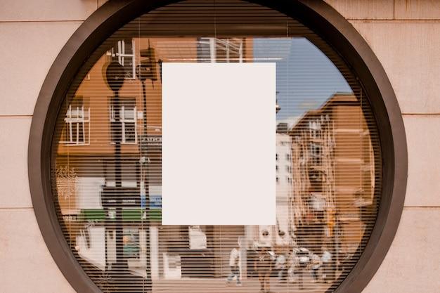 Libro blanco en blanco en la ventana de vidrio circular Foto gratis