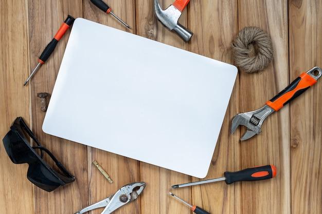 Libro blanco y herramientas manuales en piso de madera. Foto gratis