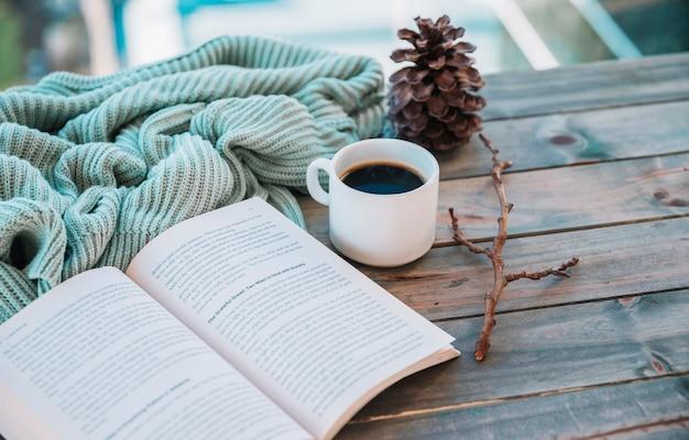Libro cerca de taza y textil de lana en mesa. Foto gratis
