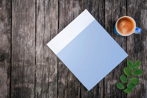 Libro de la cubierta en blanco de la maqueta y taza de café azul en viejo fondo de madera. Foto Premium