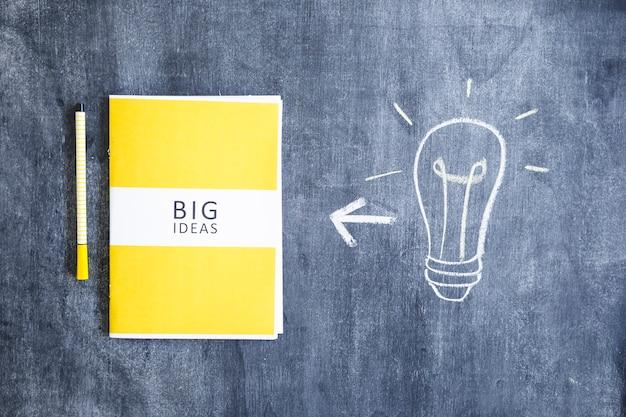 Libro de grandes ideas con rotulador y bombilla dibujada a mano en ...