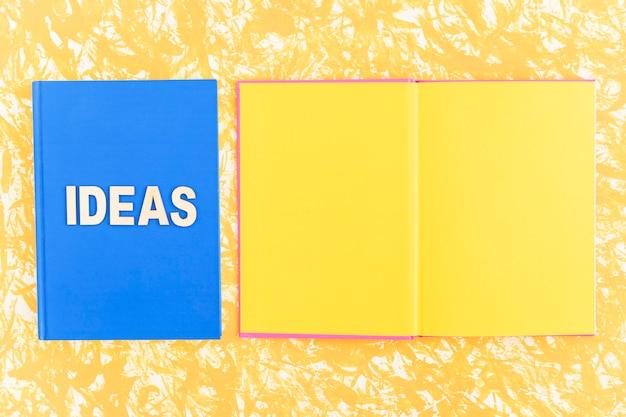 Libro de ideas cerca del libro de páginas amarillas sobre fondo amarillo Foto gratis