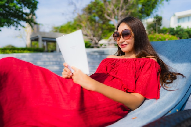 Libro de lectura asiático joven hermoso de la mujer del retrato en piscina en el hotel y el centro turístico Foto gratis