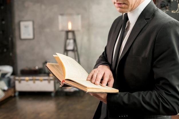 Libro de lectura elegante adulto del hombre de negocios Foto gratis