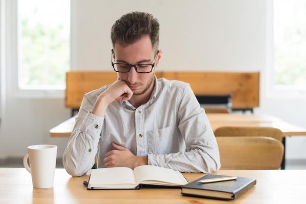 Libro de lectura enfocado del estudiante masculino en el escritorio en sala de clase Foto gratis