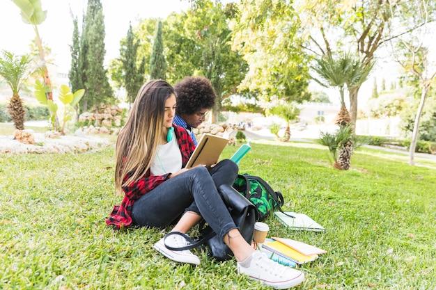 Libro de lectura feliz de los pares del estudiante en parque el día de primavera Foto gratis