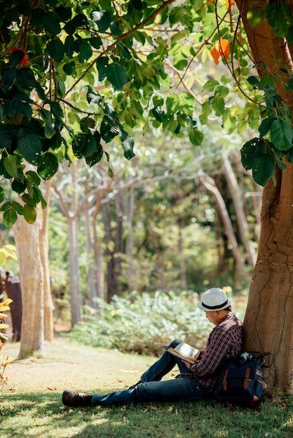 Libro de lectura del hombre joven en el césped en verano Foto gratis